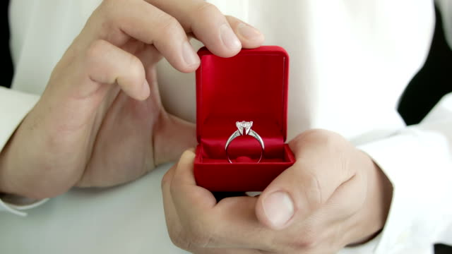 Man making proposal with wedding ring.