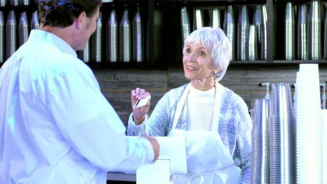 stockvideo's en b-roll-footage met man maken aankoop in koffie shop - 70 79 jaar