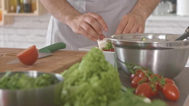 man making salad in kitchen - feta stock videos & royalty-free footage