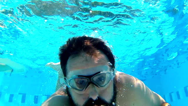 vídeos de stock e filmes b-roll de man making selfie diving in swimming pool - mergulhar para a água
