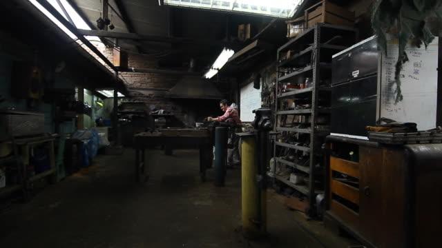 stockvideo's en b-roll-footage met ms pan man making spurs in his workshop / santiago, chile - wiese