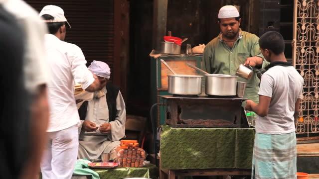ms man making tea at tea stall / delhi, india   - marktstand stock-videos und b-roll-filmmaterial