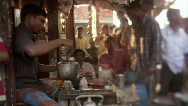 ms, selective focus, man making tea in tea shop, people standing in line in doorway, mawna, bangladesh - dhaka stock videos and b-roll footage