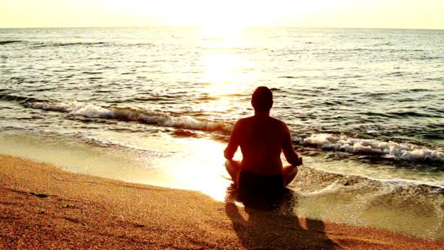 Man making yoga at seaside