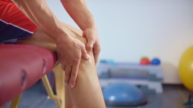 vídeos de stock, filmes e b-roll de slo mo man massageando a perna por causa da dor - massage table