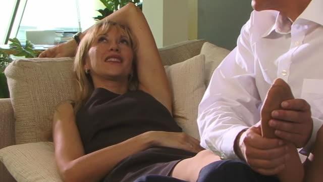 ms, man massaging woman's feet on sofa - massage room stock videos & royalty-free footage