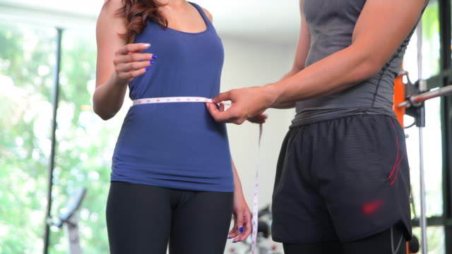 man measure slim girl waist with measuring tape in fitness - measuring stock videos & royalty-free footage