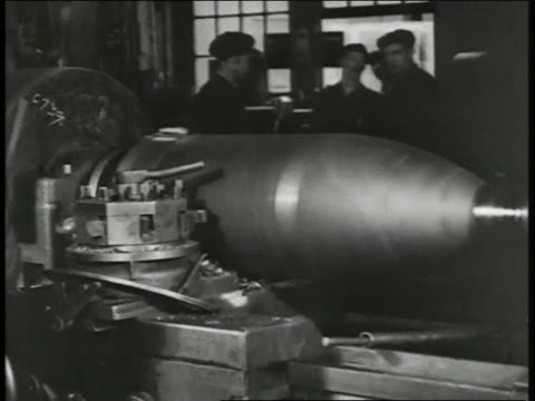 man measuring bomb casing or large shell casing spinning on machine men moving artillery shells on conveyor rollers many shells standing - 1917 stock videos & royalty-free footage