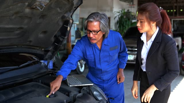 a man mechanic and woman customer discussing repairs done to her vehicle. - car mechanic stock videos & royalty-free footage