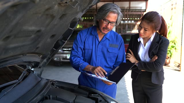 a man mechanic and woman customer discussing repairs done to her vehicle. - laboratorio riparazioni video stock e b–roll