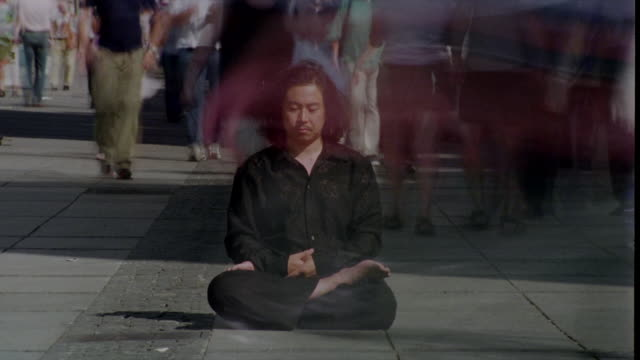 A man meditates as a crowd rushes around him.