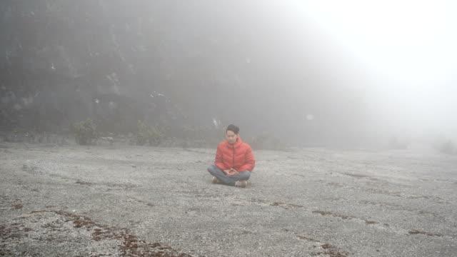 vidéos et rushes de homme méditant dans le brouillard - assis en tailleur