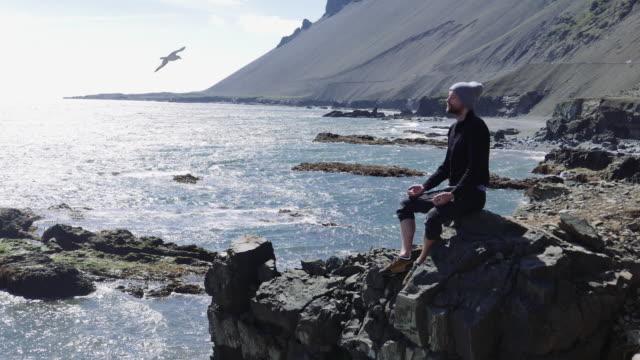 Man mediteren op een rotsachtige kust