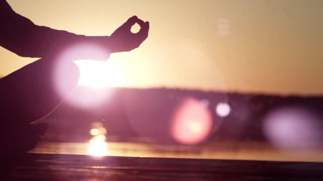 vídeos de stock e filmes b-roll de man meditating on lake pier. sunset - one mid adult man only