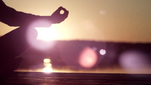 man meditating on lake pier. sunset - back lit stock videos & royalty-free footage