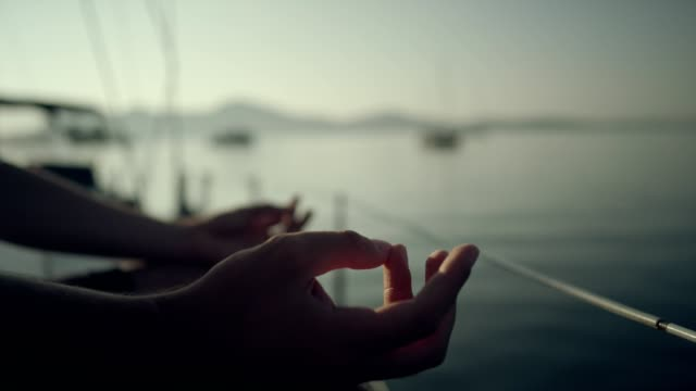 man meditating on yacht. hands. - yachting stock videos & royalty-free footage
