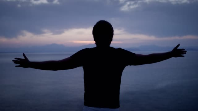 man meditating with open arms. rocky coastline - person cross legged stock videos & royalty-free footage