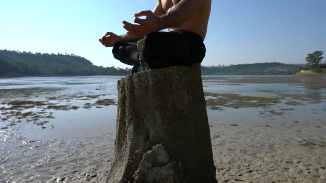 Man meditating yoga by the lake