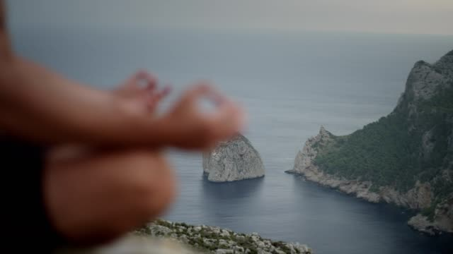 man meditation on rocky coastline. close up on hands. - mudra stock videos & royalty-free footage