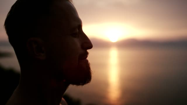 man meditation. rocky coastline at sunset - guardare in una direzione video stock e b–roll