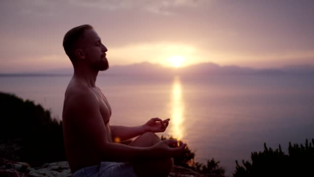 man meditation. rocky coastline at sunset - mindfulness stock videos & royalty-free footage