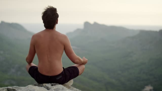 man meditation. rocky coastline - a petto nudo video stock e b–roll