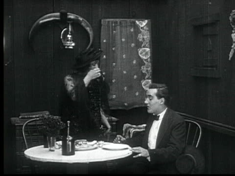 1916 b/w montage cu ms ws pan man meeting woman and walking indoors, drinking sitting at table, woman embracing and kissing him while other man eavesdrops through wall, 1880s / santa monica, california, usa - flirting stock videos & royalty-free footage
