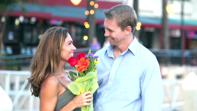 Man meeting woman, gives flowers