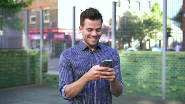 vídeos de stock e filmes b-roll de man messaging back and forth, thinking and responding on smart phone - telefone móvel