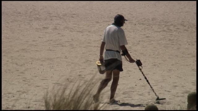 vidéos et rushes de (hd1080) homme en métal sur la plage détection - metal