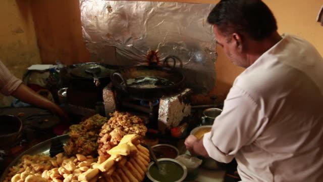 Man mixing gramflour into a utensil, Delhi, India