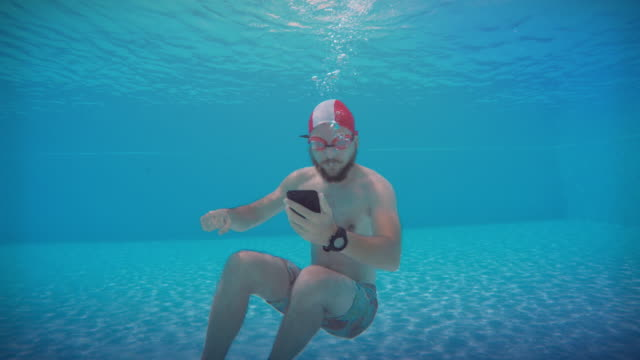 Man mobile gaming with phone underwater