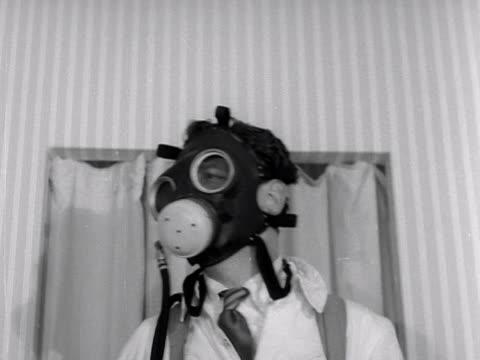 a man models breathing equipment at a factory equipment exhibition - ガスマスク点の映像素材/bロール