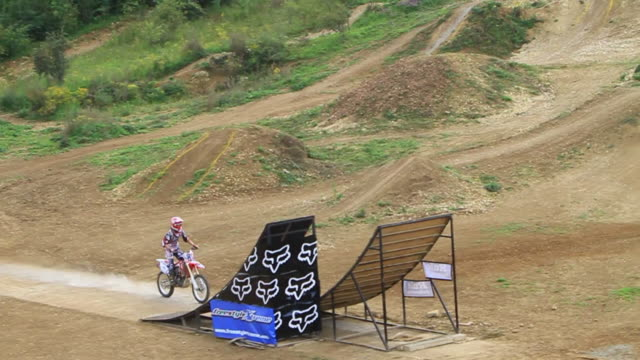 A man motocross motorcycle riding and doing a jumping trick.