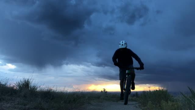 vidéos et rushes de vélos de montagne de l'homme à travers des paysages naturels ciel du désert - nouveau mexique