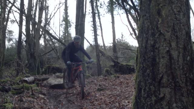A man mountain biking in the woods.