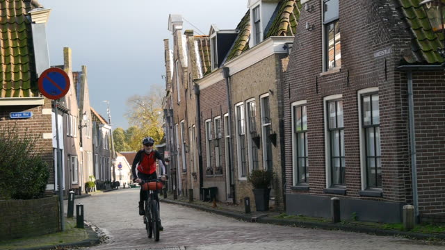 stockvideo's en b-roll-footage met a man mountain biking through the streets of a small european city. - nederland
