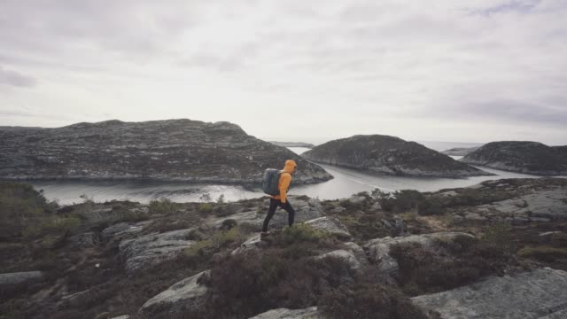 stockvideo's en b-roll-footage met bergwandelen van de man door een fjord in noorwegen - individualiteit