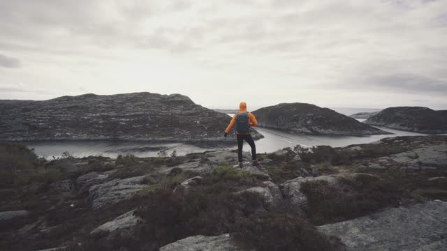 man mountain hiking by a fjord in norway - top garment stock videos & royalty-free footage