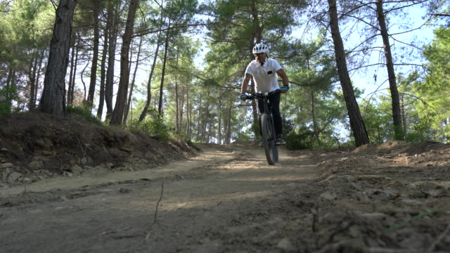 man mountainbiker rides on a sports bicycle on a forest trail. - dirt road stock videos and b-roll footage
