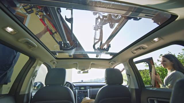 vidéos et rushes de bicyclette de montage d'homme sur le porteur de toit de voiture - loisir