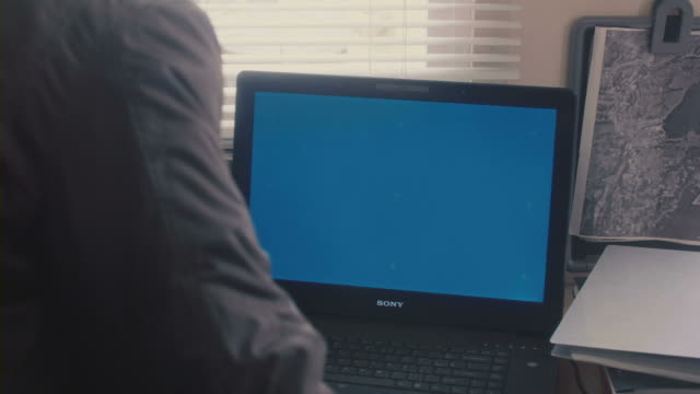 A man moving in front of a laptop.