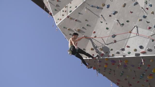 man moving up at climbing wall / gwangjin-gu, seoul, south korea - kletterwand kletterausrüstung stock-videos und b-roll-filmmaterial
