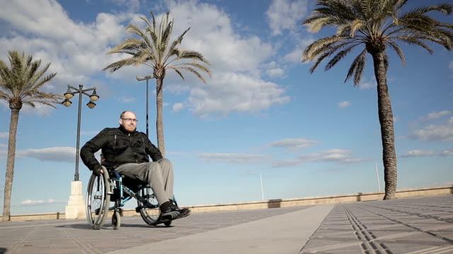 vídeos de stock e filmes b-roll de man moving wheelchair - stock video - paralisia