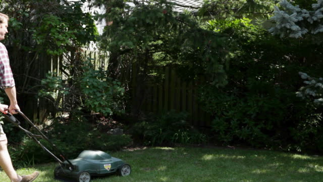 man mowing grass with lawnmower - one young man only stock videos & royalty-free footage