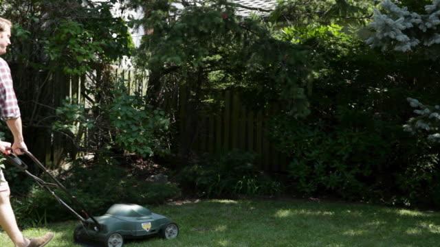 vídeos y material grabado en eventos de stock de man mowing grass with lawnmower - one young man only