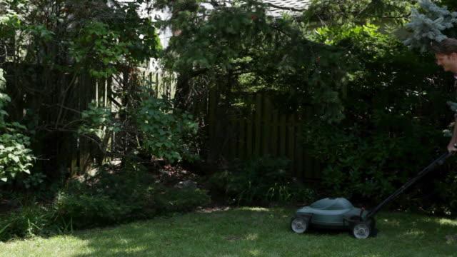 vídeos de stock e filmes b-roll de man mowing grass with lawnmower - só um homem jovem