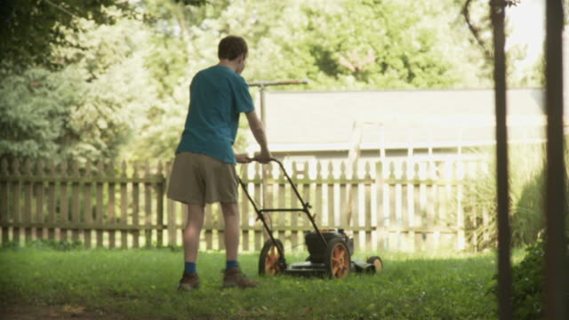 ws slo mo man mowing lawn in front of picket fence / new orleans, louisiana, usa - tosaerba video stock e b–roll