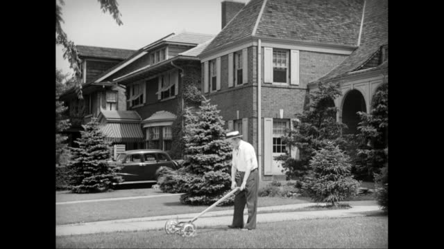 ws pan man mowing lawn of suburban house / united states - suburban stock videos & royalty-free footage