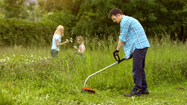 ls man mowing lawn with a weed trimmer - mowing stock videos & royalty-free footage